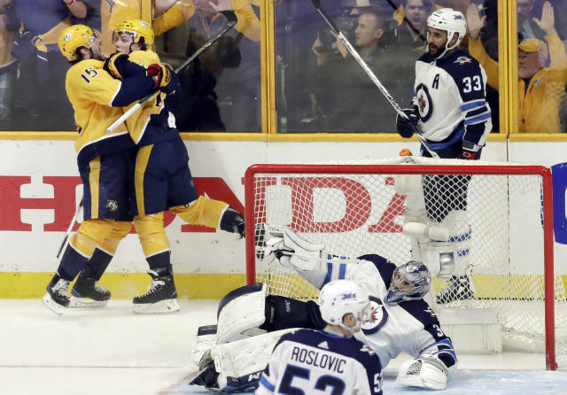 Nashville Predators left wing Kevin Fiala, second from left, of Switzerland, celebrates with Craig Smith (15) as Winnipeg Jets defenseman Dustin Byfuglien (33) skates by after Fiala scored the winning goal against goalie Connor Hellebuyck (37) during the second overtime in Game 2 of an NHL hockey second-round playoff series, Sunday, April 29, 2018, in Nashville, Tenn. The Predators won 5-4 to tie the series 1-1. (AP Photo/Mark Humphrey)