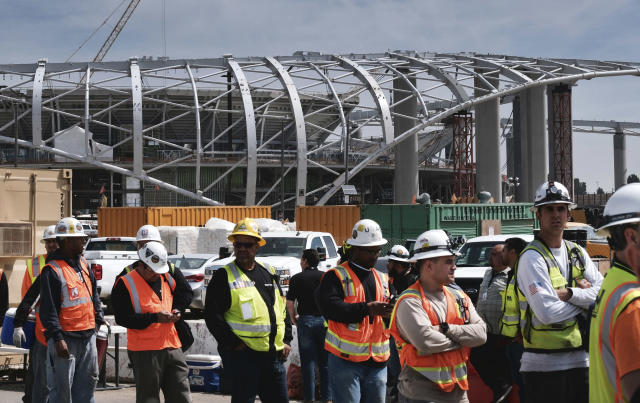 Construction workers arrive for lunch prior to an LA football stadium topping-out ceremony in Inglewood, Calif. on Monday April 15, 2019. Stadium officials hosted a tour for the media after the final piece of the canopy structure to hold the roof was completed. (AP Photo/Richard Vogel)