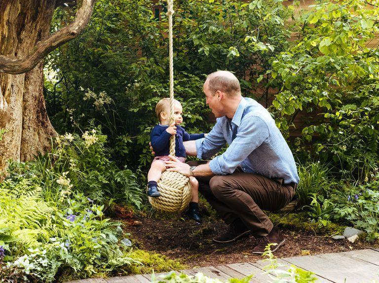 """<p>William helps little Louis play on a swing <a href=""""https://www.townandcountrymag.com/society/tradition/a27520757/kate-middleton-william-george-charlotte-louis-photos-chelsea-flower-show/"""" rel=""""nofollow noopener"""" target=""""_blank"""" data-ylk=""""slk:in the new garden designed"""" class=""""link rapid-noclick-resp"""">in the new garden designed</a> by Kate Middleton at the Chelsea Flower Show. The space was created to encourage families to spend time in nature. </p>"""
