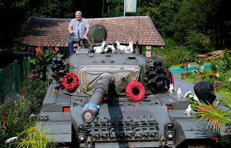 """Gary Blackburn, a 53-year-old tree surgeon from Lincolnshire, Britain, poses atop of a demilitarised Centurion tank he bought from the Swiss army at his British curiosities collection called """"Little Britain"""" in Linz-Kretzhaus, south of Germany's former capital Bonn, Germany, August 24, 2017. REUTERS/Wolfgang Rattay"""