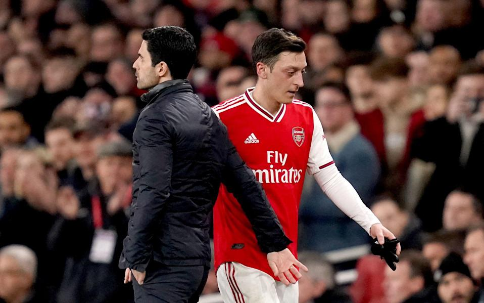 Mesut Ozil leaving the pitch with Mikel Arteta - PA