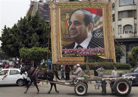 An Egyptian man on horse cart rides past a huge banner for Egypt's former army chief Field Marshal Abdel Fattah al-Sisi in downtown Cairo