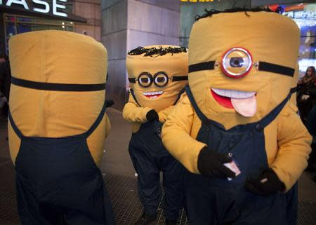 Mascots dressed up as the Minion characters from the movie 'Despicable Me' wait for people to take a photo with them for tips on Thanksgiving in New York November 28, 2013. REUTERS/Carlo Allegri