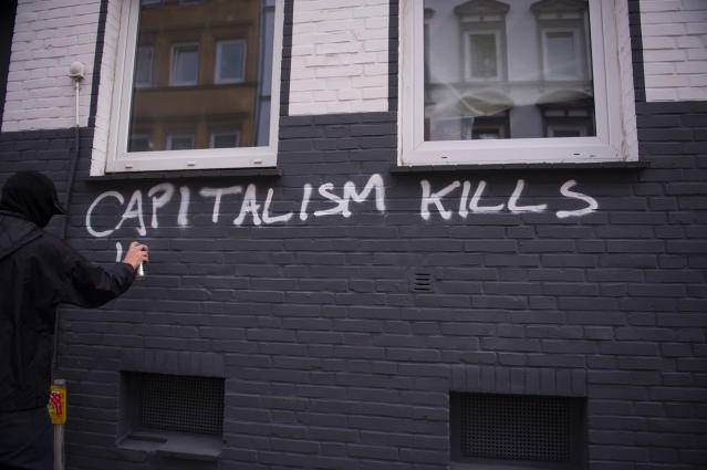 <p>A protester writes on the wall on July 7, 2017 in Hamburg, northern Germany, where leaders of the world's top economies gather for a G20 summit. (Photo: Steffi Loos/AFP/Getty Images) </p>