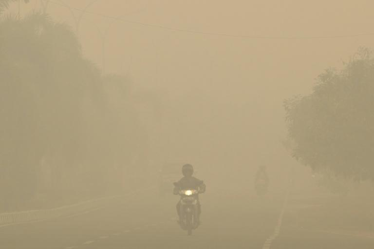 Motorists drive through thick haze in Palembang, on Indonesia's Sumatra island in September 2015