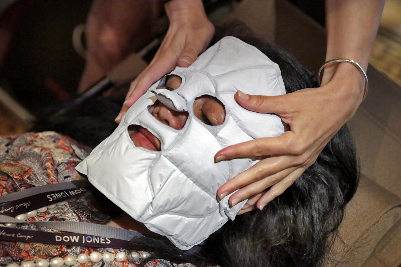 In this July 27, 2016 photo, Jamie Palazzolo, of Chaleur Beauty from Henderson, NV, applies one of their Self-Heating Facial Masks at the annual International SPA Association event, in New York. (AP Photo/Richard Drew)