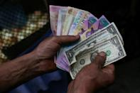 A market trader shows different currency notes in Caracas -- cash is a rare commodity in a country used to digital payments