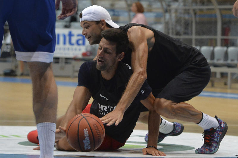 Grigor Dimitrov, rear, plays basketball with Novak Djokovic last Thursday in Croatia. (AP Photo/Zvonko Kucelin)