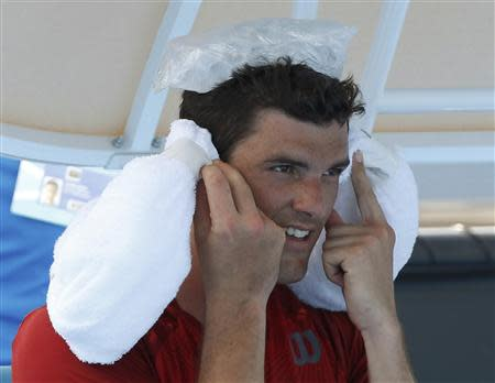 Frank Dancevic of Canada keeps cool with ice packs during a break in play in his men's singles match against Benoit Paire of France at the Australian Open 2014 tennis tournament in Melbourne January 14, 2014. REUTERS/Brandon Malone