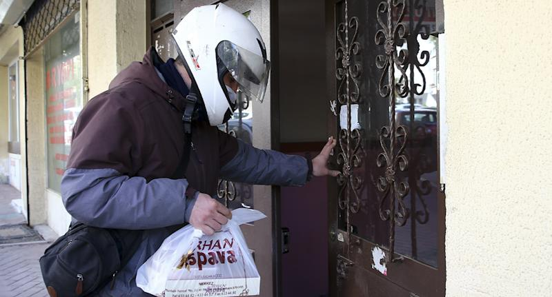 Photo shows a food delivery being made to someone's front door.