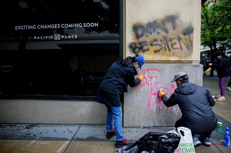 Community members help clean debris and graffiti the morning after a rally against the death in Minneapolis police custody of George Floyd, in Seattle