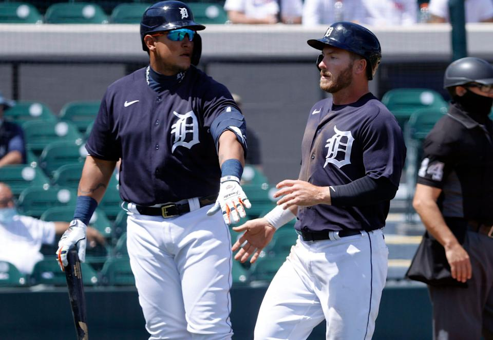 Detroit Tigers outfielder Robbie Grossman, right, is congratulated by Miguel Cabrera as he scores a run during the first inning against the New York Yankees at Joker Marchant Stadium, March 23, 2021 in Lakeland, Fla.