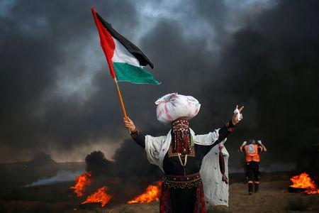 A woman holds a Palestinian flag during a protest calling for lifting the Israeli blockade on Gaza and demand the right to return to their homeland, at the Israel-Gaza border fence, east of Gaza City September 14, 2018. REUTERS/Mohammed Salem