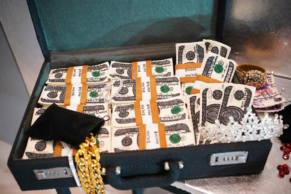 Lit by the headlights of the police car, we see the contents of the bank vault, including millions of dollars in cash, passports and jewellery (Yui Mok/PA) (PA Wire)