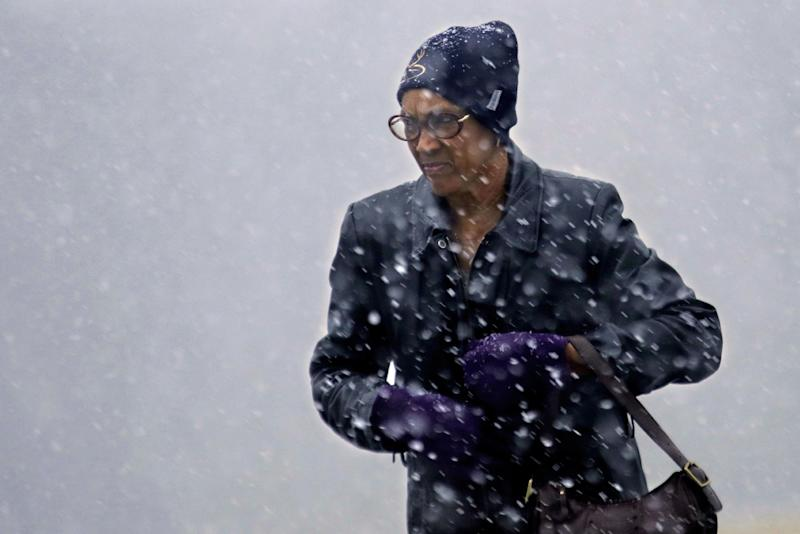 A woman struggles against strong winds and falling snow as a fast moving winter storm moves into the Midwest Friday, Dec. 13, 2013, in Springfield, Ill. A winter weather advisory extends from Missouri to western New York, according to the National Weather Service. Boston and most of southern New England may see 6 to 12 inches of snow while areas just north and east of the New York may get as much as 10 inches. (AP Photo/Seth Perlman)