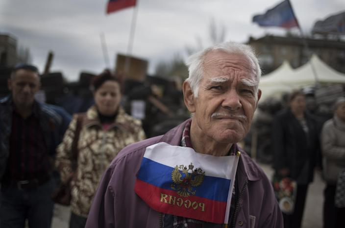 A man holds a Russian national flag as he and the others listen to a pro-Russian activist at barricades in front of a regional administration building that was seized by pro-Russian activists earlier in Donetsk, Ukraine, Sunday, April 20, 2014. The Ukrainian and Russian governments are reporting a shootout at a checkpoint set up by pro-Russian insurgents in eastern Ukraine that has left one person dead and others hospitalized with gunshot wounds. (AP Photo/Alexander Zemlianichenko)