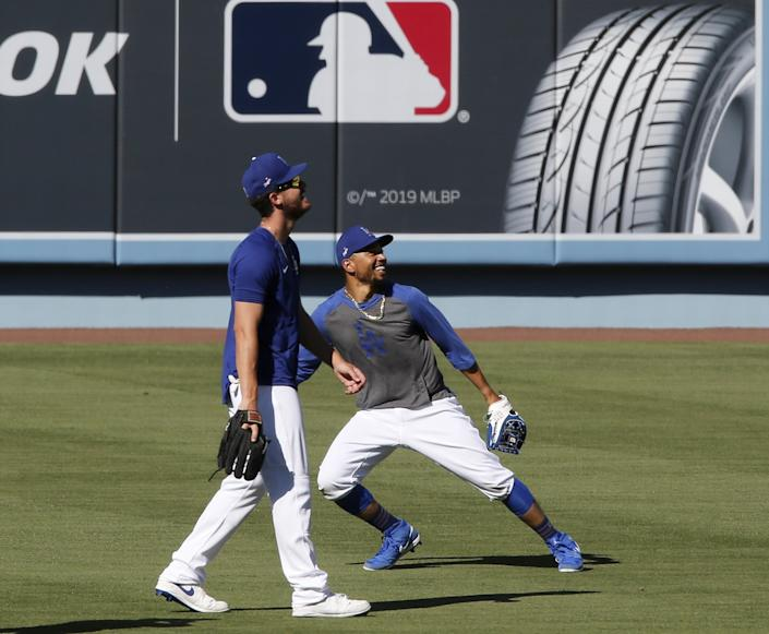 "Dodgers right fielders Cody Bellinger, left, and Mookie Betts catch fly balls during practice at Dodger Stadium on Friday. <span class=""copyright"">(Luis Sinco / Los Angeles Times)</span>"