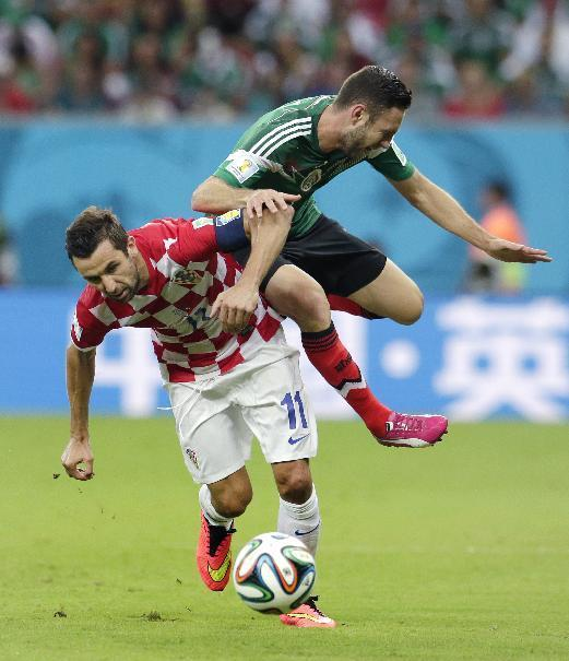 Croatia's Darijo Srna , left, and Mexico's Miguel Layun battle for the ball during the group A World Cup soccer match between Croatia and Mexico at the Arena Pernambuco in Recife, Brazil, Monday, June 23, 2014. (AP Photo/Petr David Josek)