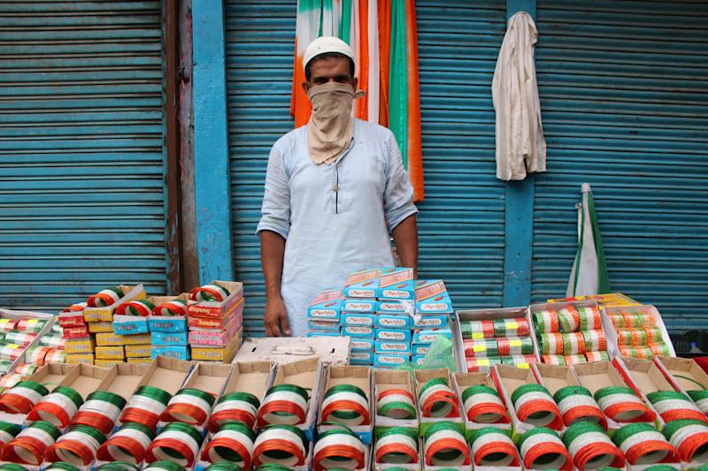 A vendor with face mask as a precautionary measure against Covid-19, sells tri-coloured bangles ahead of Independence Day celebrations at Lal Kuan on August 12, 2020 in Delhi, India. (Photo by Mayank Makhija/NurPhoto via Getty Images)