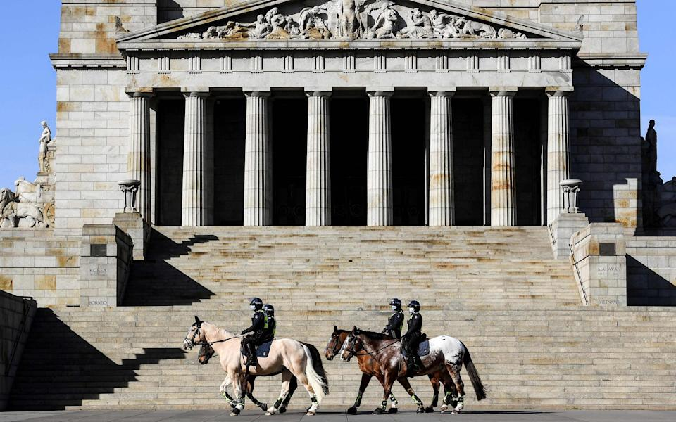Police on horseback patrol The Shrine of Remembrance enforcing people to wear masks in Melbourne - WILLIAM WEST/AFP