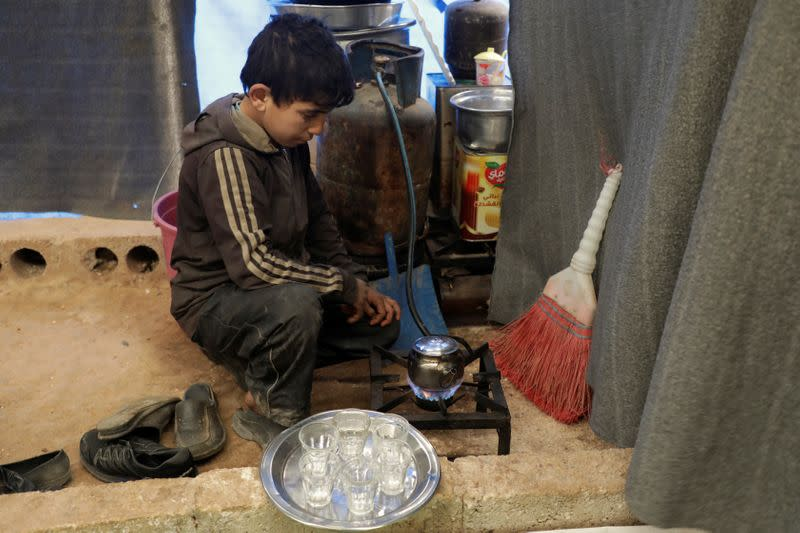 Mohammed Abu Rdan prepares tea inside a tent, at an internally displaced Syrian camp, in northern Aleppo