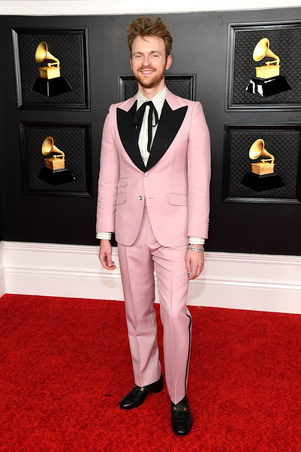 <p>Wearing a pink and black suit.</p>