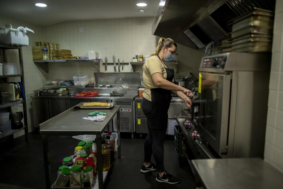 Rocio Sanchez works in the kitchen at La Francachela restaurant in Madrid, Spain, Friday, March 26, 2021. Experimenting with cutting back one workday per week is about to go nationwide in Spain. A 3-year pilot project will be using 50 million euros ($59 million) from the European Union's massive coronavirus recovery fund to compensate companies as they resize their workforce or reorganize production workflows to adapt to a 32-hour working week. (AP Photo/Manu Fernandez)