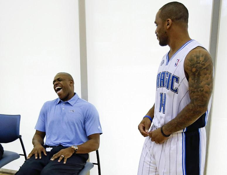 Orlando Magic's Jameer Nelson, right, jokes with former Magic player Nick Anderson, now with the Orlando Magic's community relations department, at the team's NBA basketball media day, Monday, Sept. 30, 2013, in Orlando, Fla. (AP Photo/John Raoux)