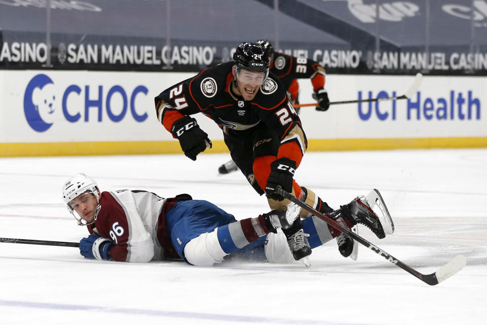 Anaheim Ducks forward Carter Rowney (24) falls over Colorado Avalanche forward Mikko Rantanen (96) during the first period of an NHL hockey game in Anaheim, Calif., Friday, Jan. 22, 2021. (AP Photo/Ringo H.W. Chiu)