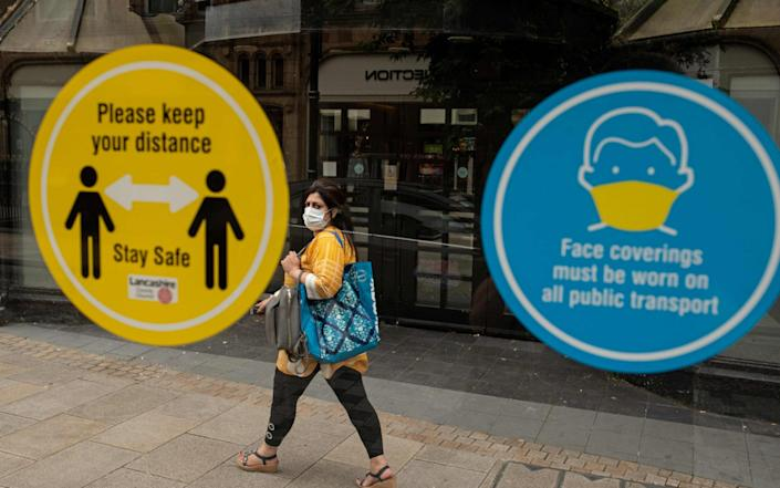 In this file photo taken on August 08, 2020 A woman walks past notices on a bus shelter advising people to maintain a social distance and wear face coverings, in the city centre of Preston, north west England, as local lockdown restrictions are reimposed due to a spike in cases of the novel coronavirus in the city - Oli Scarff/AFP