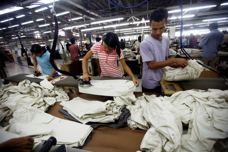 FILE PHOTO: Workers iron and arrange clothing at a garment factory at Hlaing Tar Yar industry zone in Yangon