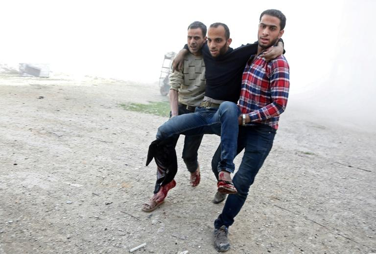 Syrians help carry a man wounded in shelling of the rebel-held besieged town of Ayn Tarma in the eastern Ghouta region on the outskirts of the capital