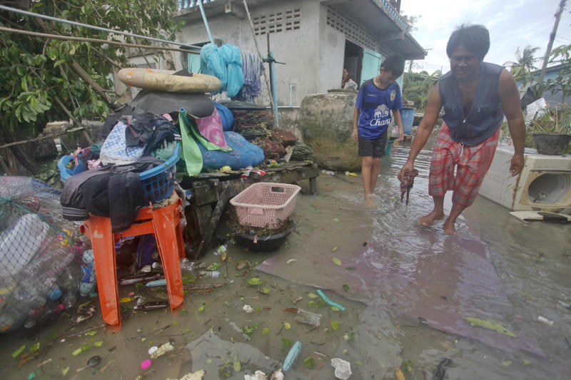 Thai people recover belongings in the aftermath of Tropical Storm Pabuk Saturday, Jan. 5, 2019, in Pak Phanang, in Thailand's southern province of Nakhon Si Thammarat. The storm damaged houses, knocked down power lines and triggered flash floods in several east coast provinces. (AP Photo/Sumeth Panpetch)