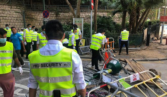 Security guards clear barricades at the Eastern main gate of the University of Hong Kong on Bonham Road. Photo: Lilian Cheng