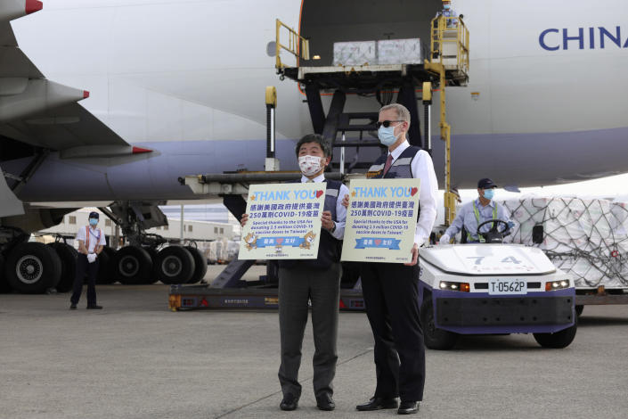 In this photo released by the Taiwan Centers for Disease Control, Taiwan's Health Minister Chen Shih-chung, left, and Brent Christensen, the top U.S. official in Taiwan, hold up thank you cards as they welcome a China Airlines cargo plane carrying COVID-19 vaccines from Memphis that arrived at the airport outside Taipei in Taiwan Sunday, June 20, 2021. The U.S. sent 2.5 million doses of the Moderna COVID-19 vaccine to Taiwan on Sunday, tripling an earlier pledge in a donation with both public health and geopolitical meaning. (Taiwan Centers for Disease Control via AP)