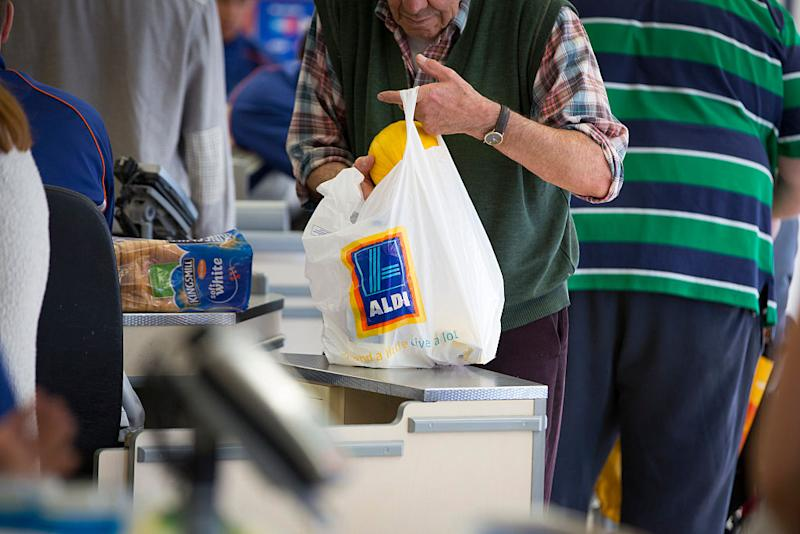 A customer places a melon into a plastic carrier bag, branded with the Aldi name. Source: Getty