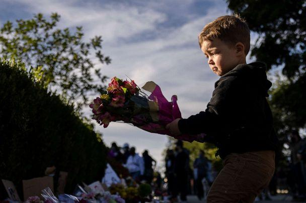 PHOTO: A young boy places flowers at a makeshift memorial in honor of Supreme Court Justice Ruth Bader Ginsburg at the U.S. Supreme Court on Sept. 19, 2020. (Samuel Corum/Getty Images)