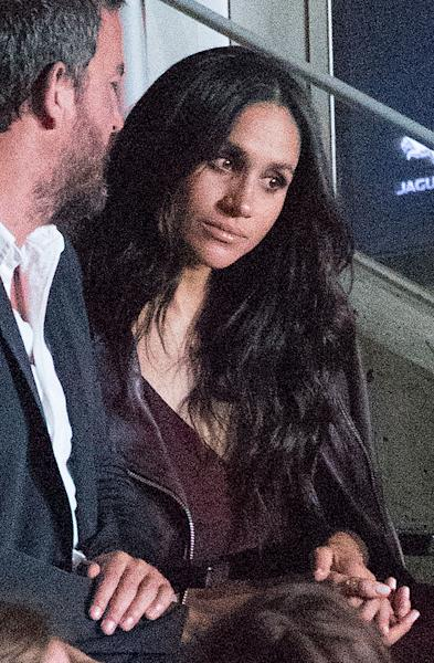 <p>Markle listened closely while talking with her friend Markus Anderson.</p>