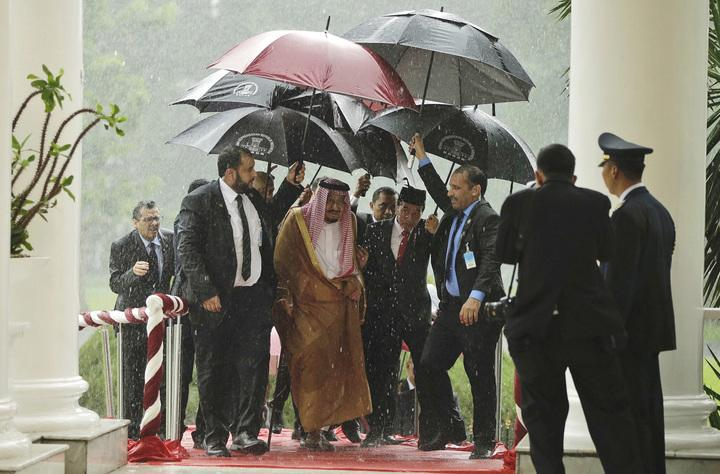King Salman and Indonesian President Joko Widodo walk under umbrellas during heavy rain at the presidential palace in Bogor, West Java, Indonesia (Credit: AP/REX/Shutterstock)