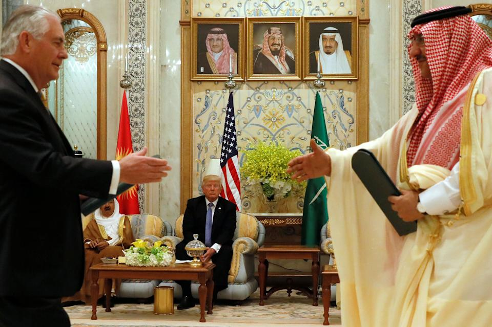 Trump looks on as Secretary of State Tillerson (left) and Crown Prince Muhammad bin Nayef (right) exchange a memorandum of understanding, in which the Gulf states commit not to finance militant organizations, at the Gulf Cooperation Council leaders summit in Riyadh on May 21, 2017.
