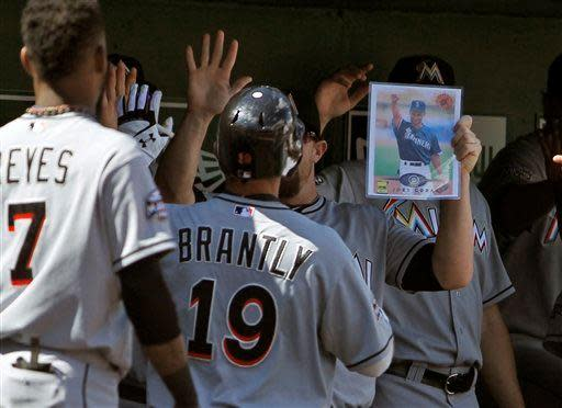 A teammate holds a photo of Milwaukee Brewers' Joey Cora as Miami Marlins' Rob Brantly celebrates his score during the second inning of a baseball game against the Washington Nationals at Nationals Park, Sunday, Sept. 9, 2012, in Washington. (AP Photo/Alex Brandon)