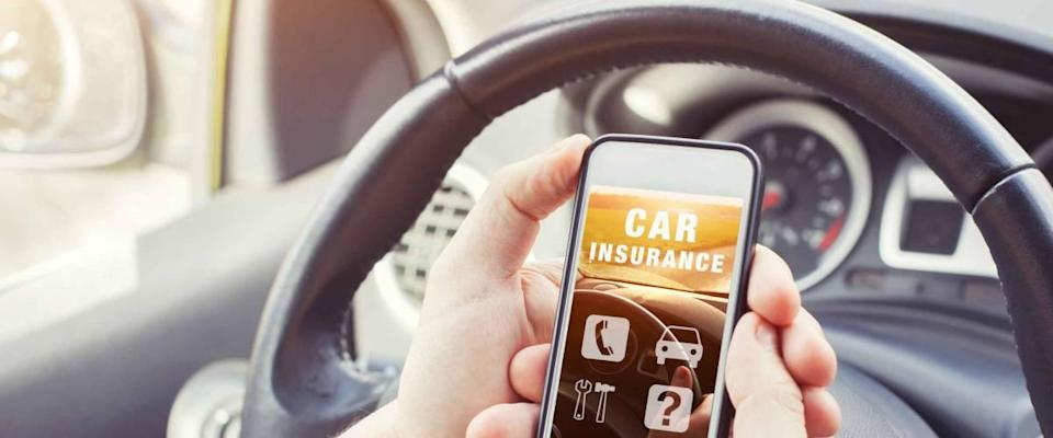 Driver looks at car insurance website on smartphone