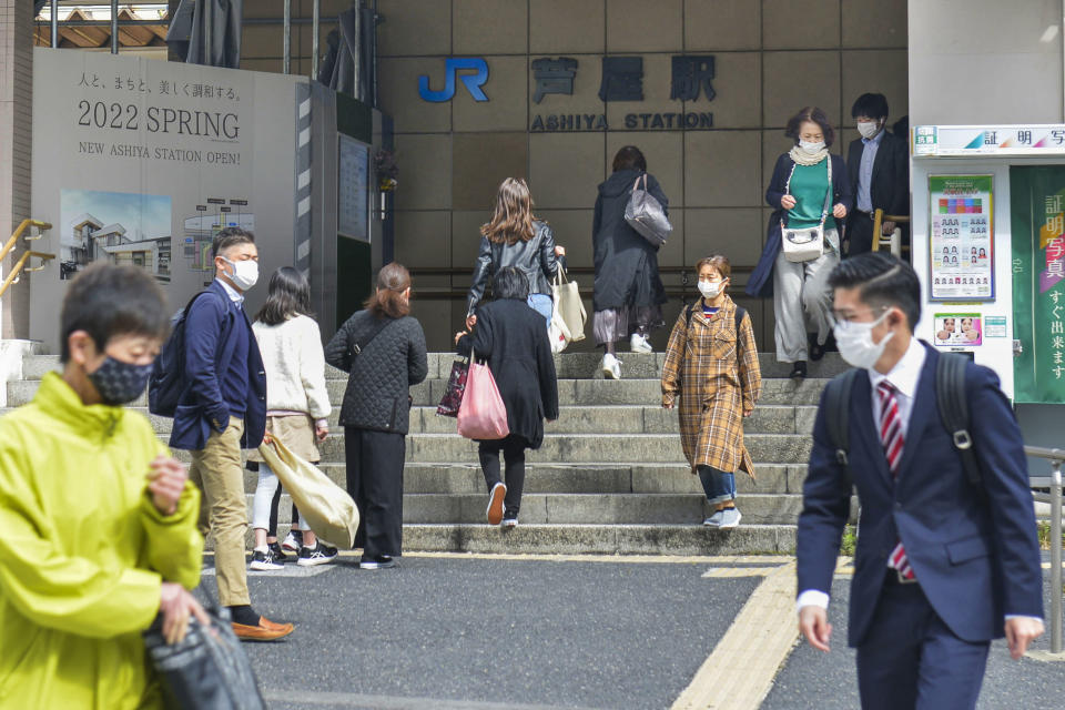 People wearing face masks to help curb the spread of the coronavirus walk in front of Ashiya train station in Ashiya, Hyogo prefecture, western Japan, Monday, April 5, 2021. Semi-emergency coronavirus measures began in Osaka and its neighboring prefecture in western Japan and another prefecture in the north Monday as Japan tries to minimize the economic impact to specific areas where infections are rising back less than four months before the Tokyo Olympics. (Yumi Ozaki/Kyodo News via AP)