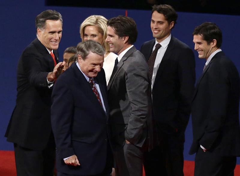 FILE - This Oct. 3, 2012 file photo shows Republican presidential candidate, former Massachusetts Gov. Mitt Romney patting moderator Jim Lehrer on the back at the end of the first presidential debate with President Barack Obama in Denver. When it comes to debates, Mitt Romney loves the rules. The eyes of millions of voters upon him, the Republican candidate is quick to poke holes in his rival's arguments. But he's just as ready to take the moderator to task when he believes the predetermined ground rules have been breached. Also pictured, from right to left: Matt Romney, Craig Romney, Tagg Romney, Ann Romney. (AP Photo/Charles Dharapak, File)