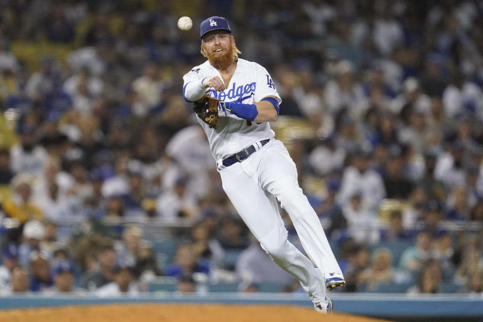 Los Angeles Dodgers third baseman Justin Turner (10) throws to first during the third inning of a baseball game against the Milwaukee Brewers Friday, Sept. 1, 2021, in Los Angeles. Milwaukee Brewers' Christian Yelich was safe at first. (AP Photo/Ashley Landis)