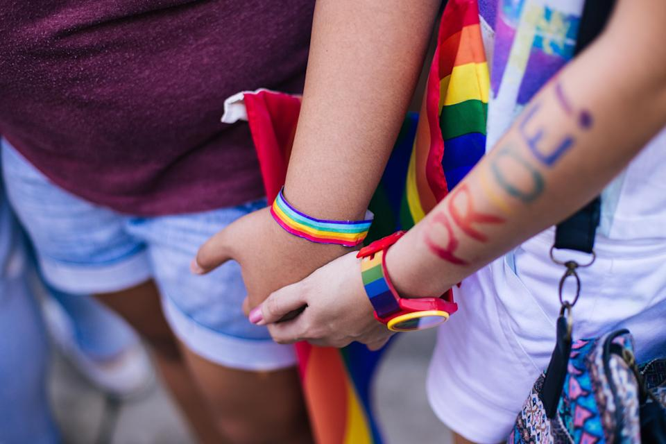 Two people holding hands at Pride celebrations. [Photo: Getty]