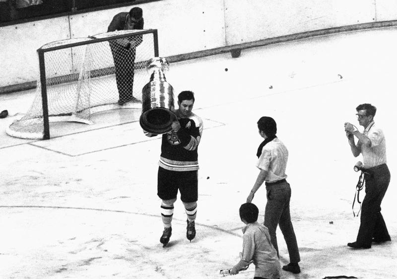 FILE - In this May 10, 1970, file photo, Boston Bruins' John Bucyk carries the Stanley Cup as he skates around the rink at Boston Garden, after the Bruins beat the St. Louis Blues 4-3 in overtime to win the cup. (AP Photo/File)