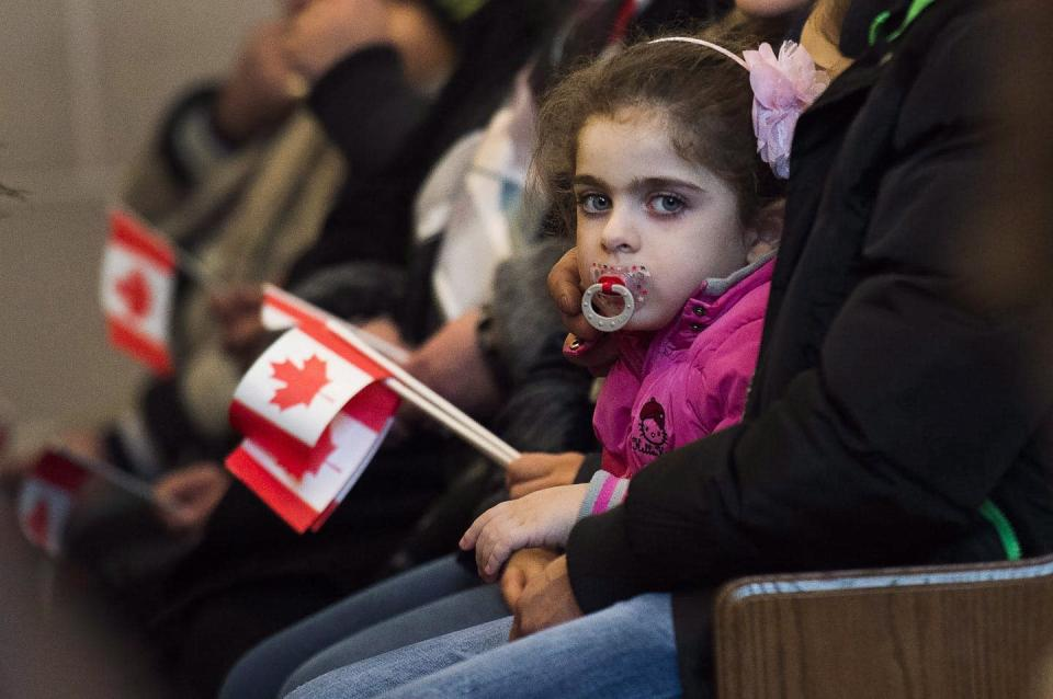 """<span class=""""caption"""">In this photo from 2015, newly arrived Syrian refugees take part in a mass at the Armenian Community Centre in Toronto. </span> <span class=""""attribution""""><span class=""""source"""">THE CANADIAN PRESS/Nathan Denette </span></span>"""