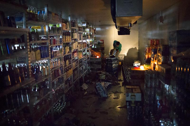 FILE - In this  Sunday, Nov. 4, 2012, file photo, a worker cleans out a walk-in refrigerator in the dark at the West Side Wine & Liquor store, in  Hoboken, New Jersey. Superstorm Sandy drove the number of people seeking unemployment benefits up to a seasonally adjusted 439,000 last week, the highest level in 18 months. The Labor Department said Thursday that weekly applications increased by 78,000 mostly because a large number of applications were filed in states damaged by the storm. People can claim unemployment benefits if their workplaces close and they don't get paid. (AP Photo/John Minchillo. File)