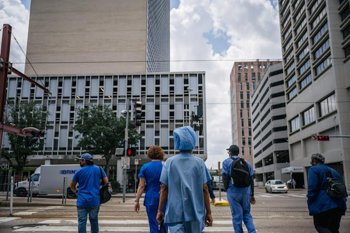 HOUSTON, TEXAS - JUNE 09: Medical workers and pedestrians cross an intersection outside of the Houston Methodist Hospital on June 09, 2021 in Houston, Texas. Houston Methodist Hospital has suspended 178 employees without pay for 14 days for their refusal to comply with its COVID-19 vaccine requirement. (Photo by Brandon Bell/Getty Images)